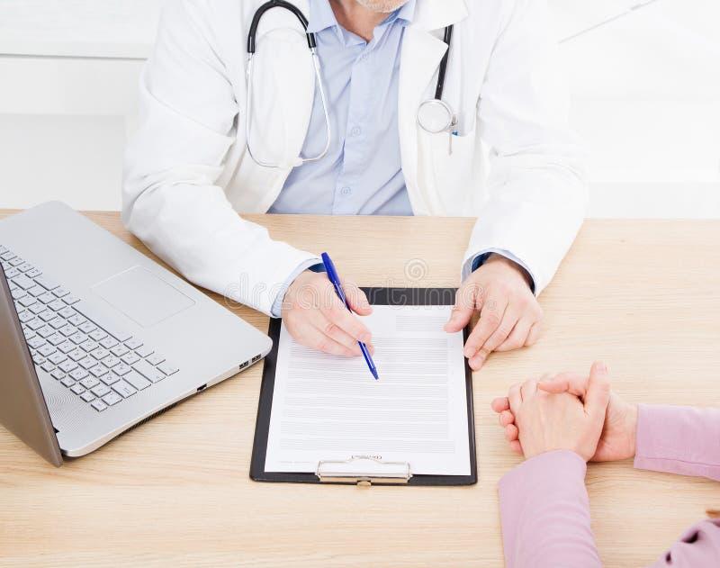 Le docteur et le patient discutent quelque chose, mains à la table images stock