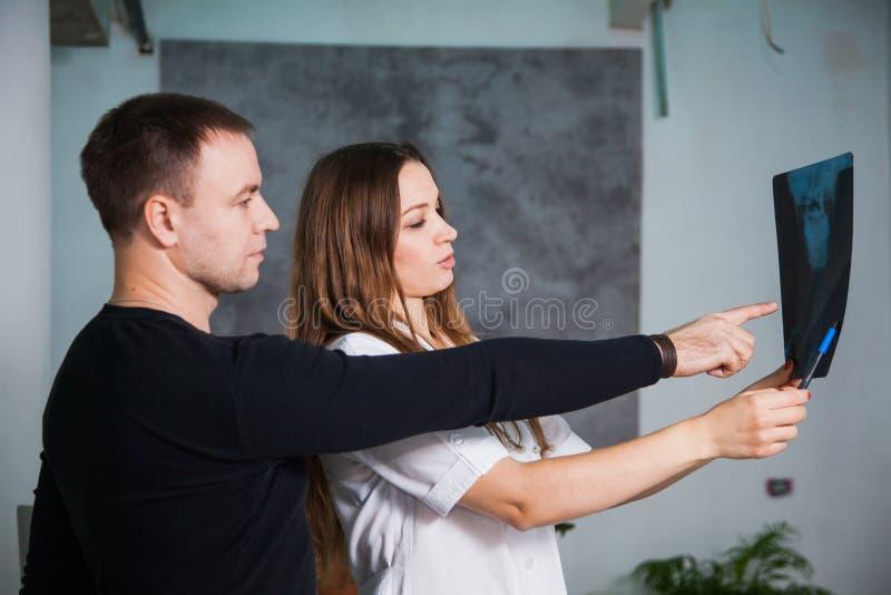 Le docteur et le patient examinent le roentgen principal à la clinique photo libre de droits