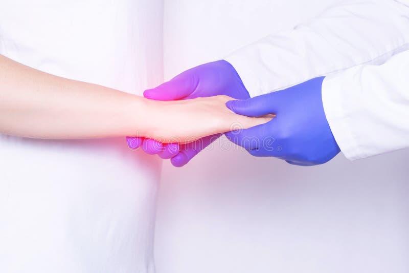 Le docteur examine le joint de poignet d'une fille pour l'entorse, l'inflammation et la douleur dans son poignet, plan rapproché, photographie stock