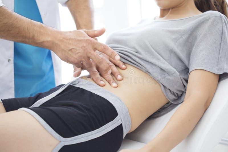 Le docteur examine l'abdomen du patient photographie stock