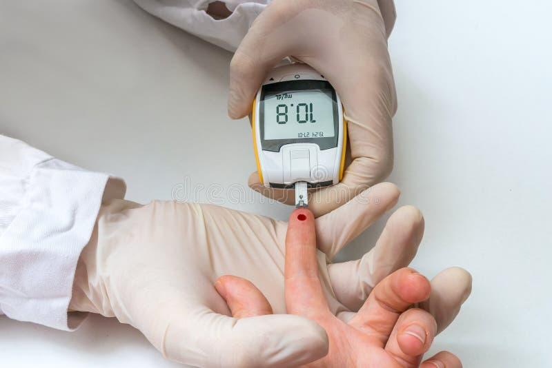 Le docteur examine le sang du patient pour le glucose et le sucre image libre de droits