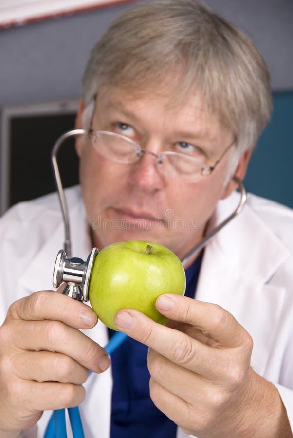 Le docteur examine une pomme photo stock