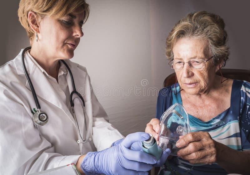 Le docteur explique à dame âgée comment des travaux de formation d'inhalation de ventimask images stock