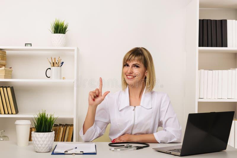 Le docteur féminin amical travaille à son bureau dans le bureau image libre de droits