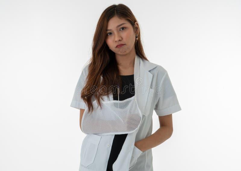 Le docteur féminin montre une expression ennuyeuse dans son bras cassé images stock