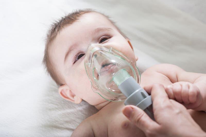 Le docteur fait l'inhalation à un petit bébé malade image stock
