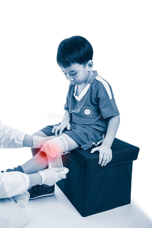 Le docteur fait le bandage sur le patient de genou, sur le fond blanc photo stock