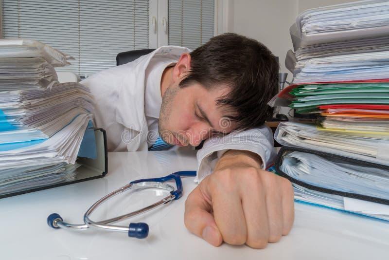 Le docteur fatigué et surchargé dort sur le bureau dans le bureau images stock