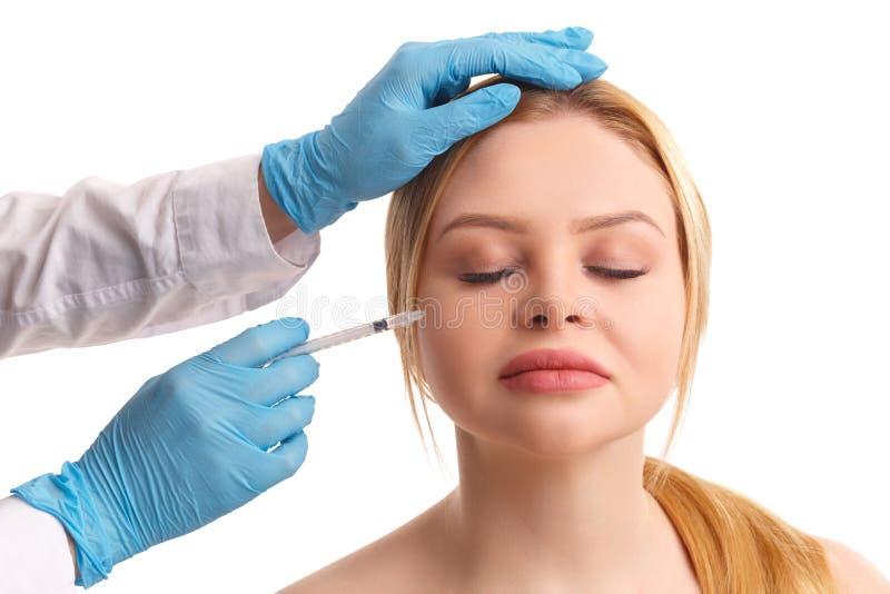 Le docteur injecte sur la joue d'une belle femme images libres de droits