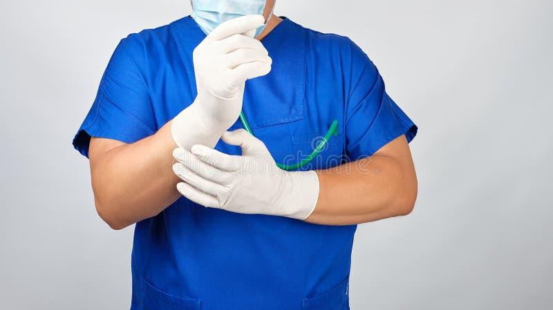 Le docteur masculin dans l'uniforme bleu met dessus ses gants stériles blancs de latex de mains images stock