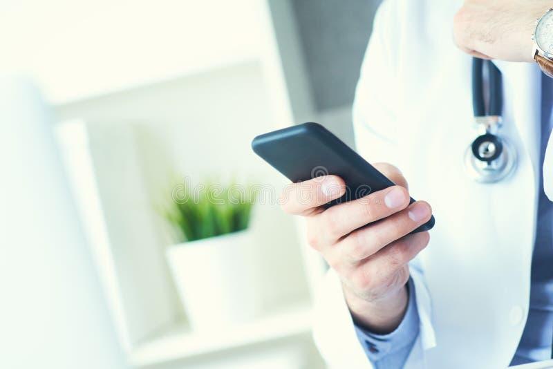 Le docteur masculin dans le manteau blanc utilise un dispositif moderne de smartphone avec l'?cran tactile Mains de docteur avec  photo libre de droits