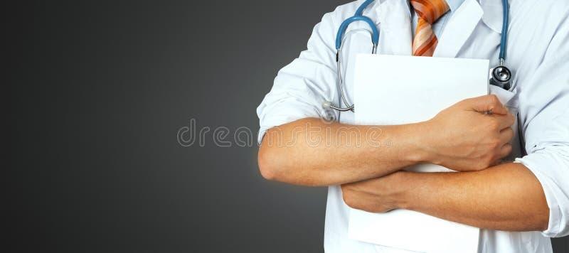 Le docteur masculin méconnaissable tient les documents médicaux sur le fond gris Médecine, soins de santé, concept d'assurance photo stock
