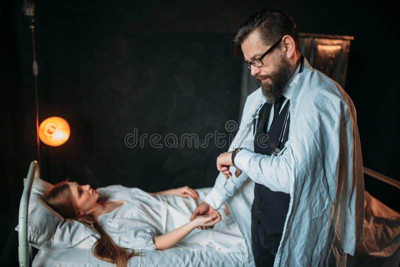 Le docteur masculin mesure l'impulsion de la jeune femme malade photo libre de droits