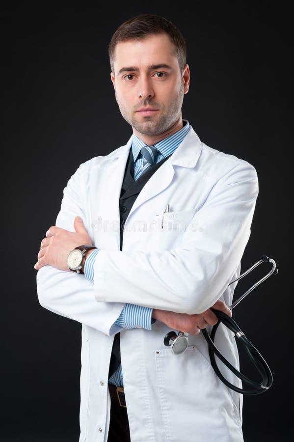 Le docteur masculin sérieux juge disponible de stéthoscope d'isolement sur le noir image stock