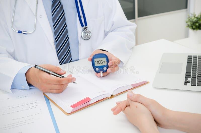 Le docteur montre le glucometer avec le niveau de glucose photo libre de droits