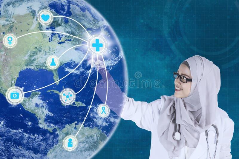 Le docteur musulman touche une icône médicale virtuelle photo libre de droits