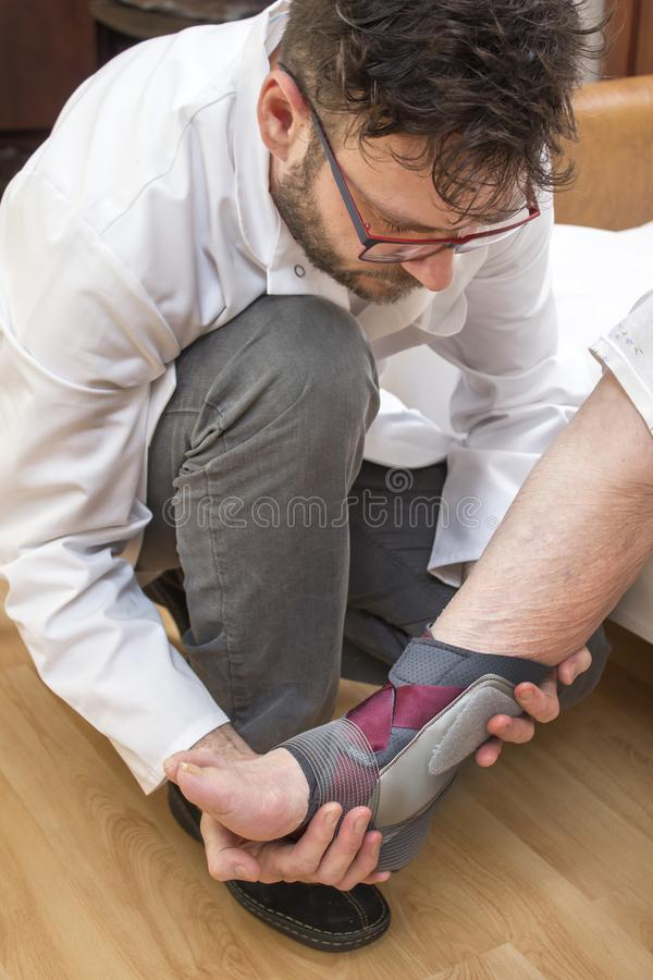 Le docteur orthopédique attachera le stabilisateur de cheville sur la jambe de dame âgée photo libre de droits
