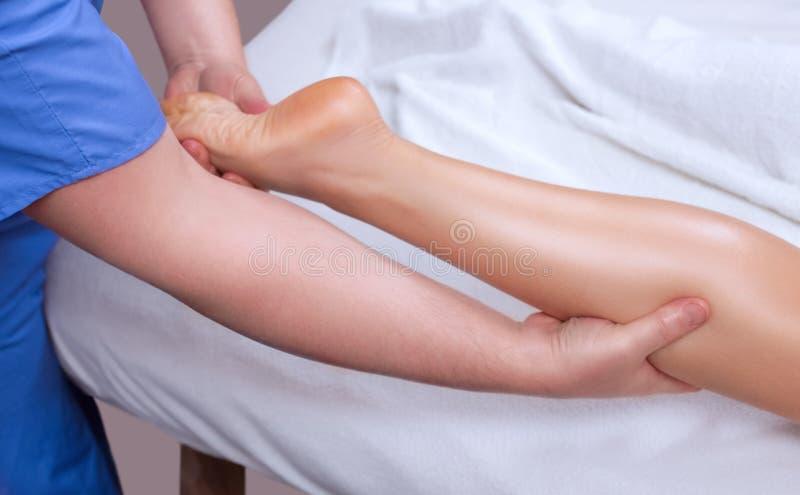 Le docteur-pédicure fait un examen et un massage du pied patient du ` s photo stock