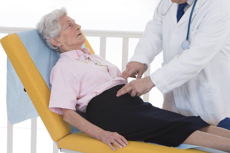 Le docteur palpent avec son abdomen de patient de mains photo stock