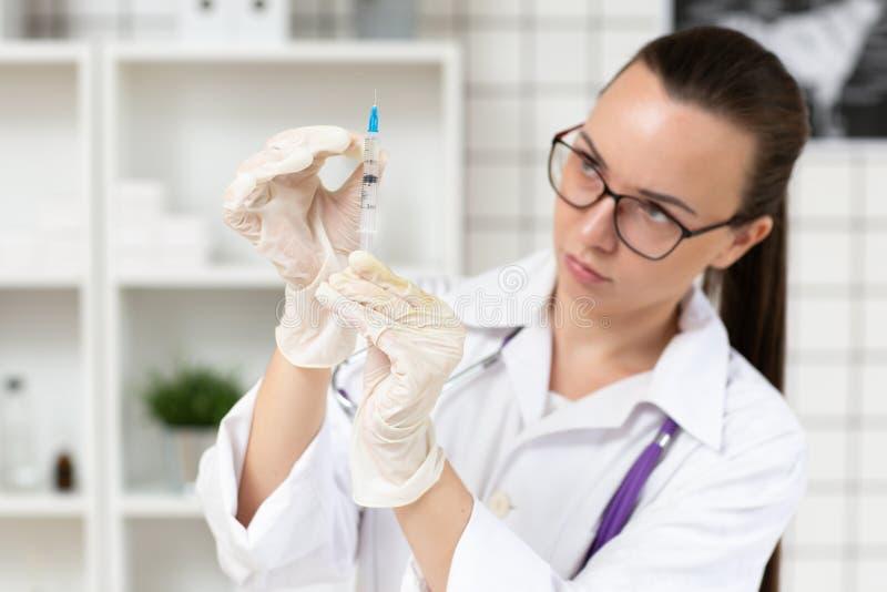 Le docteur prépare une seringue avec une solution de médecine dans la clinique Fin vers le haut Fond brouill? images stock
