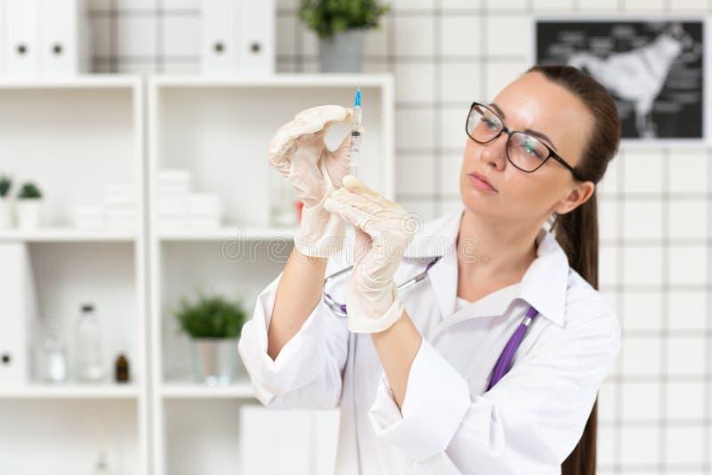 Le docteur prépare une seringue avec une solution de médecine dans la clinique Fin vers le haut Fond brouill? image stock
