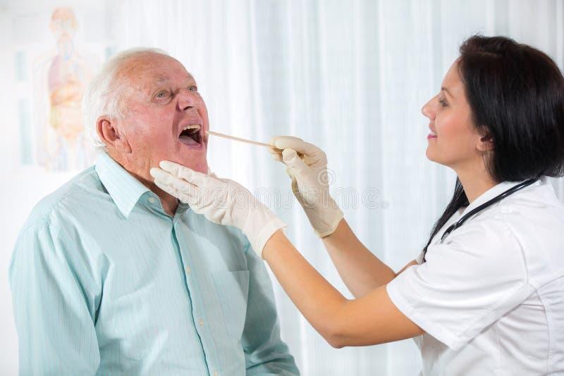 Le docteur regarde dans la gorge un homme plus âgé images libres de droits