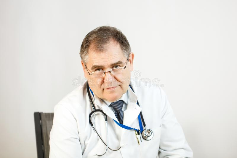 Le docteur regarde dans ses yeux, un regard sérieux, un stéthoscope autour de son cou photographie stock