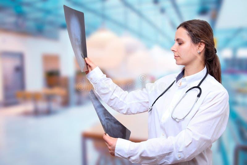 Le docteur regarde des images de rayon X sur le fond de hall de clinique photos libres de droits