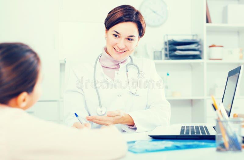 Le docteur remplit carte patiente pour la fille photos libres de droits