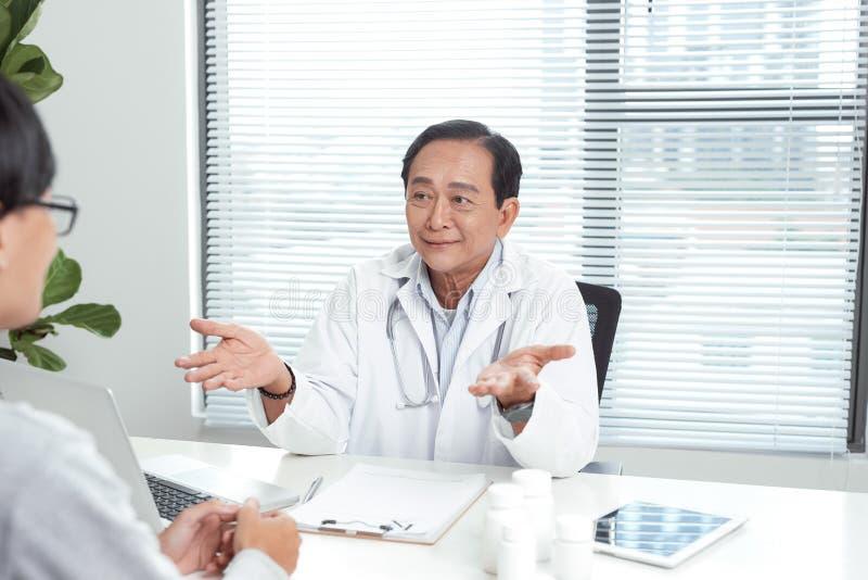Le docteur supérieur consulte le jeune patient photos libres de droits