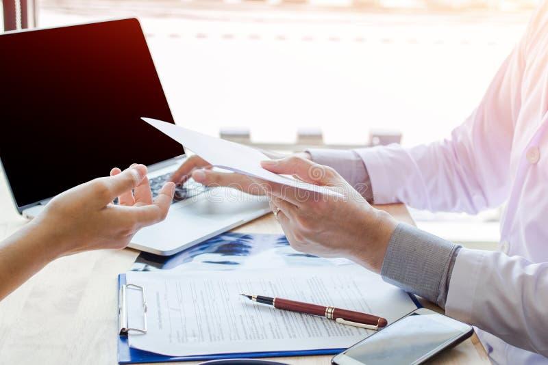 Le docteur tenant l'information sur le livre blanc et parler et conseiller patiente devrait faire attention images stock