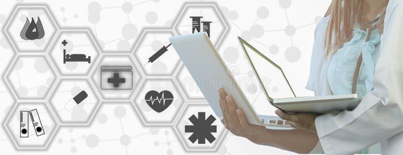 Le docteur tient l'ordinateur portable à disposition, le fond blanc d'icônes médicales, pour le style panoramique horizontal de b photo libre de droits