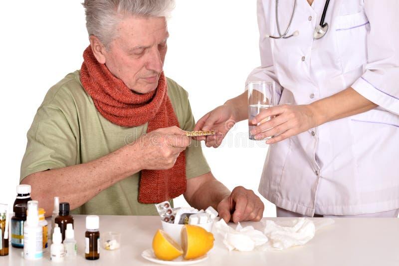 Le docteur traite l'homme plus âgé malade photographie stock