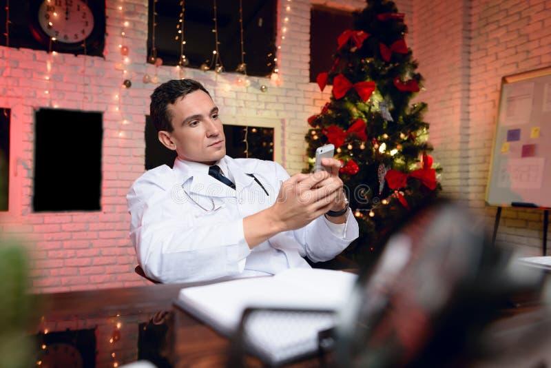 Le docteur travaille au ` s Ève de nouvelle année Il parle au téléphone photographie stock libre de droits