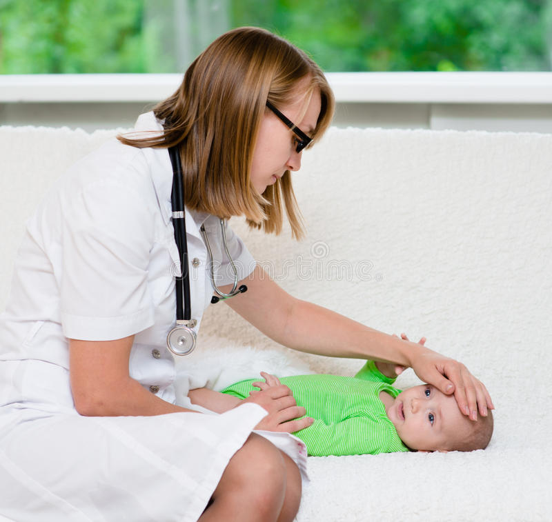 Le docteur vérifie la température du bébé touchant son front images stock