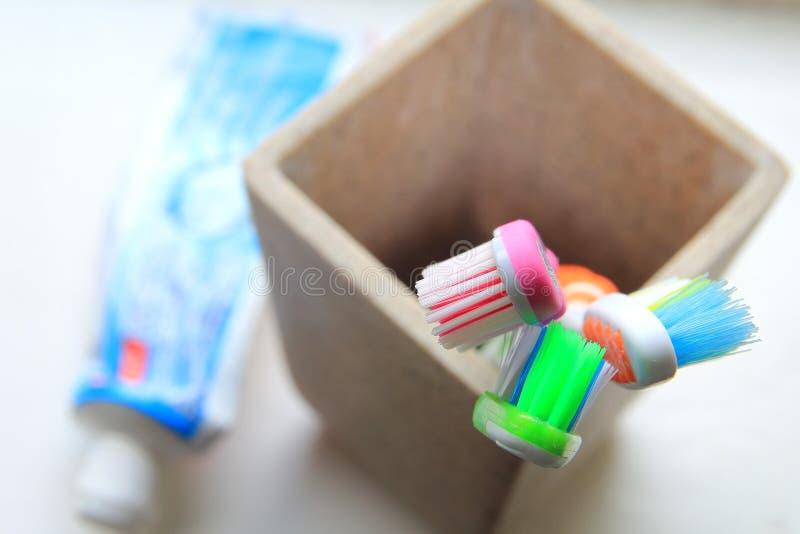 Le DOF peu profond a tiré de trois brosses à dents et pâtes dentifrices dans un culbuteur d'argile dans la lumière de matin photo libre de droits