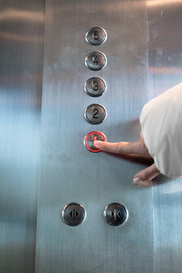 le doigt appuie sur le bouton d'ascenseur photos stock