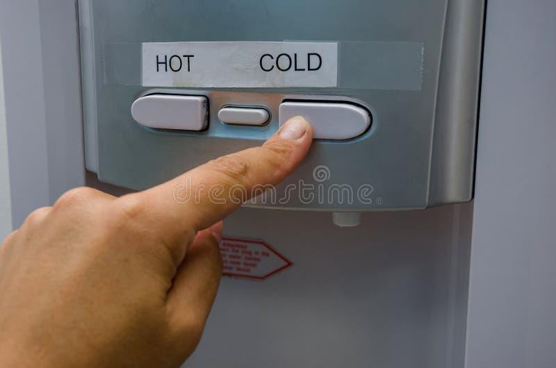 Le doigt appuie sur le bouton de l'eau chaude du refroidisseur Plan rapproch? photographie stock