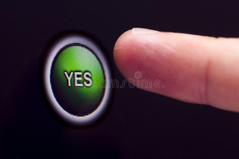 Le doigt appuie sur le bouton vert d'OUI sur l'écran tactile photographie stock libre de droits