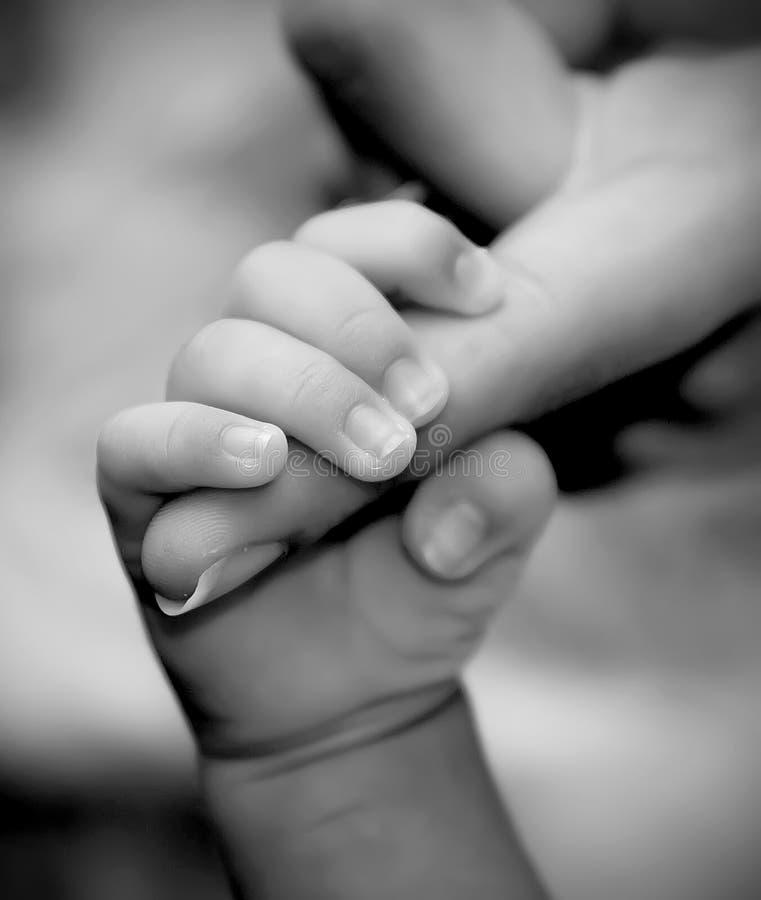 Le doigt de la mère de fixation de main de chéri image libre de droits