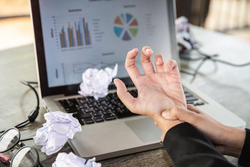 Le doigt de serrure d'une jeune femme d'affaires s'asseyant avec un ordinateur toute la journée Douleur de paume du travail avec  photos stock