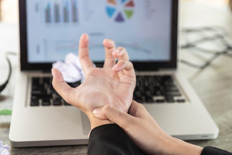 Le doigt de serrure d'une jeune femme d'affaires s'asseyant avec un ordinateur toute la journée Douleur de paume du travail avec  image stock