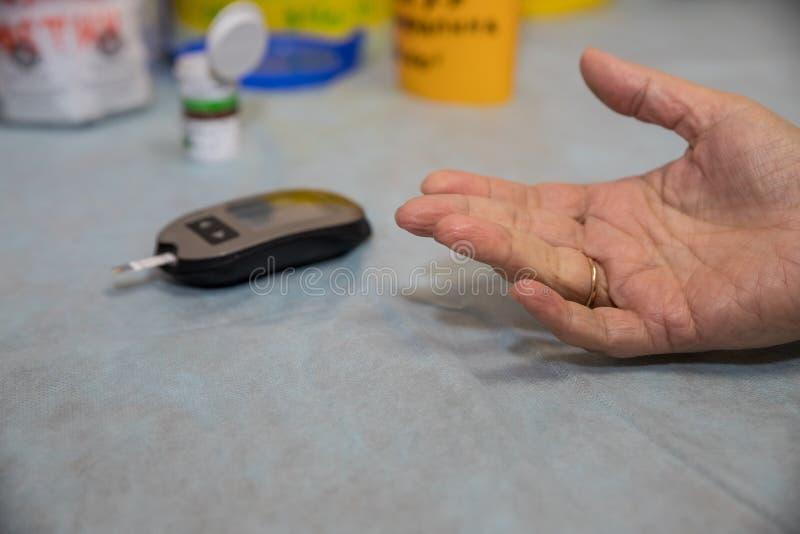 Le doigt du patient féminin supérieur de docteur Using Glucometer On La femme diabétique supérieure a un contrôle dans la cliniqu images libres de droits