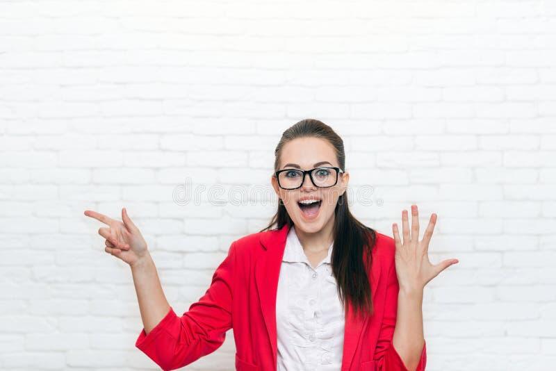 Le doigt enthousiaste de point de femme d'affaires pour copier les verres rouges de veste d'usage de l'espace sourient photographie stock libre de droits