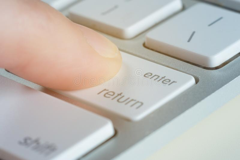 Le doigt presse introduisent la clé d'un clavier d'ordinateur images stock