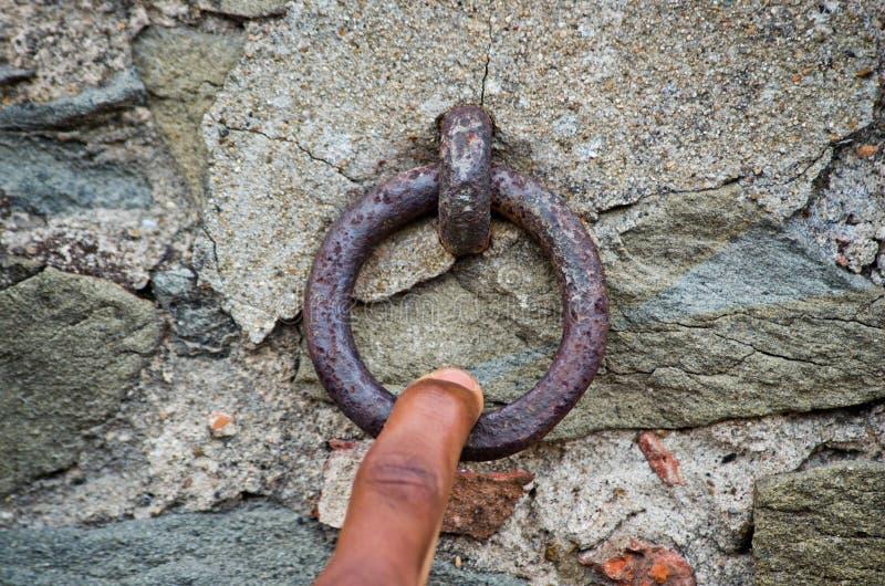 Le doigt tire un vieil anneau rouillé de fer photo libre de droits