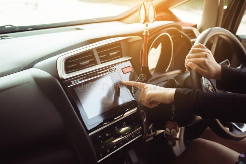 Le doigt touchant et allumant le système d'autoradio, conducteur de femme remet tenir le volant photos stock