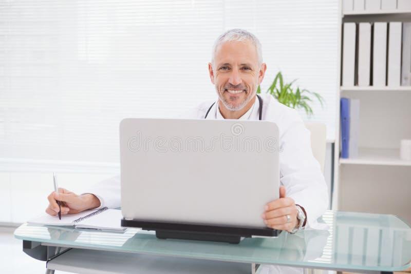 Le doktorn som använder bärbara datorn och skriva royaltyfri fotografi