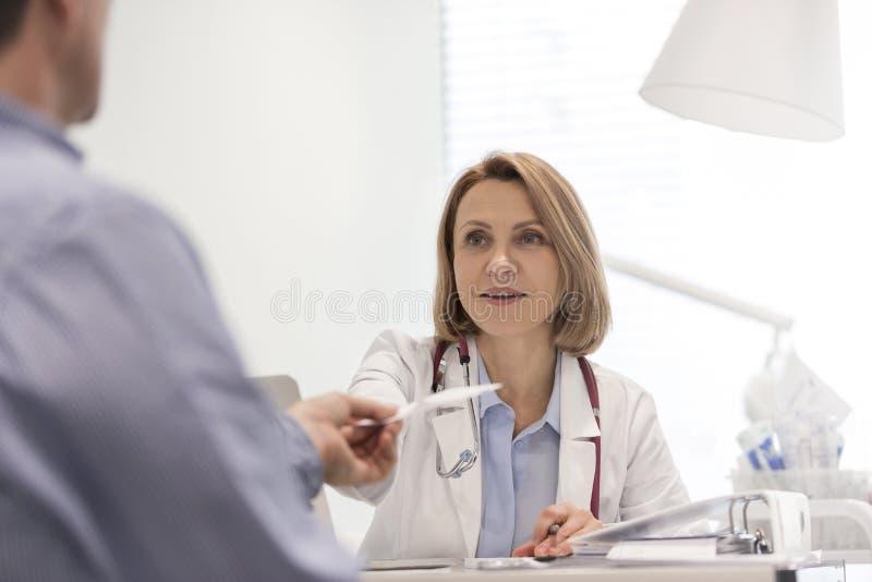 Le doktorn som ger receptet till patienten på skrivbordet i sjukhus royaltyfria bilder