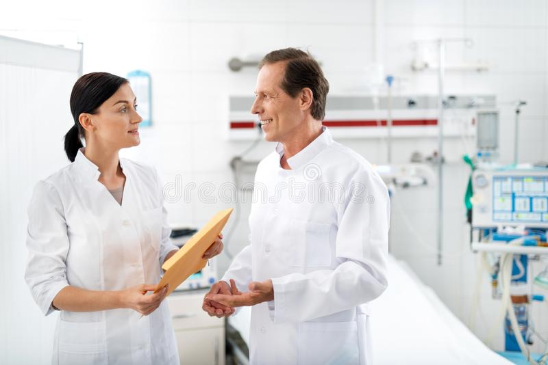 Le doktorn som talar med sjuksköterskan i sjukhusrum arkivbild